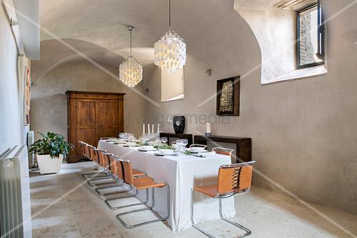 Freischwinger um gedecktem Tisch mit bodenlanger Tischdecke in renoviertem Schloss
