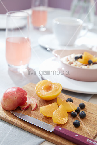 Plums and blueberries on wooden board on set breakfast table