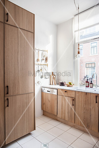 Fitted kitchen with wooden cabinets and simple accessories in natural shades
