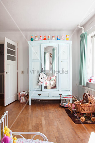Mint-green wardrobe with mirrored door and wicker dolls' pram in girl's bedroom