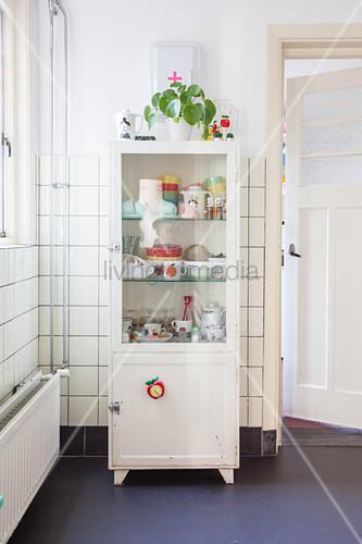 Crockery in vintage display case against tiled wall