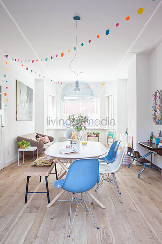 Dining table, chairs and bench in front of couch and bay window in open-plan interior