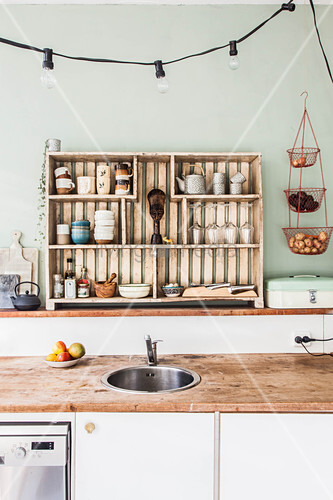 Open-fronted shelves, sink in free-standing counter and rustic worksurfaces in kitchen with pale green wall