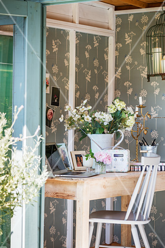 White flowers, retro radio and laptop on wooden table in summerhouse