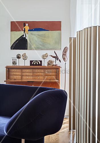 Designersofa vor Paravent aus Pappröhren und Antik Seketärkommode in offenem Wohnraum