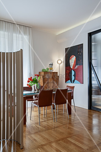 Elegant dining table and chairs in front of painting in open-plan interior divided by screen made from cardboard tubes