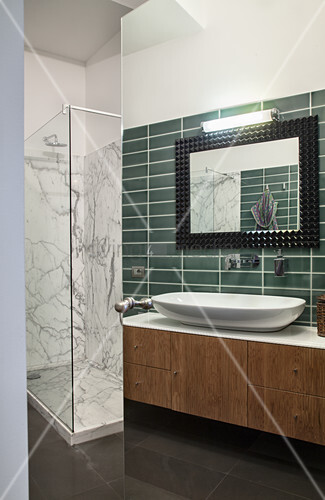 Washstand with countertop designer sink and green wall tiles next to shower cabinet with marble tiles