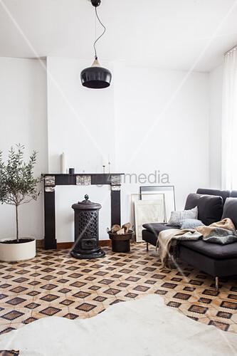 Tierfellteppich auf gemustertem Fliesenboden, graues Sofa, Holzofen vor stillgelegter Kamin und Olivenbäumchen im Wohnzimmer