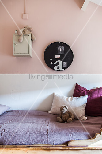 Kinderbett mit Kissen und Teddybär im Mädchenzimmer mit rosa Wand