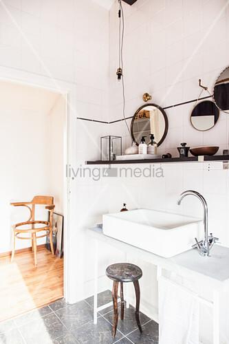Washstand with countertop sink below shelf in white bathroom