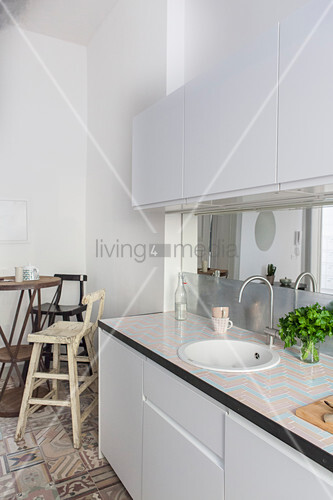 White kitchen counter and bistro table with barstools