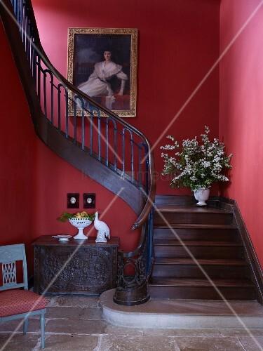 Alte Truhe unter geschwungener Holztreppe an roter Wand