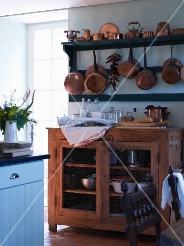 Kupfertöpfe am Regal über einem offenen Küchenschrank aus Holz