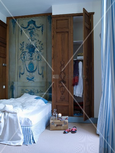 Mural protected by glass above bed next to wardrobes