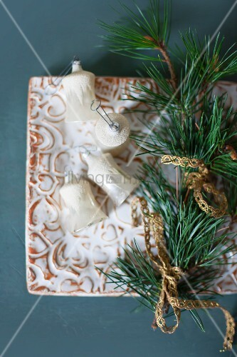 Alter Christbaumschmuck und ein Kiefernzweig mit Brokatborte