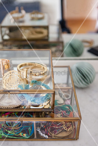 Colourful jewellery in glass and metal cases
