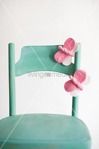 Hand-made, pink, felt butterflies on green chair