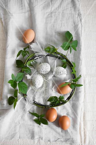 Braune und weiße, gesprenkelte Eier und Kranz aus Brombeer-Ranken