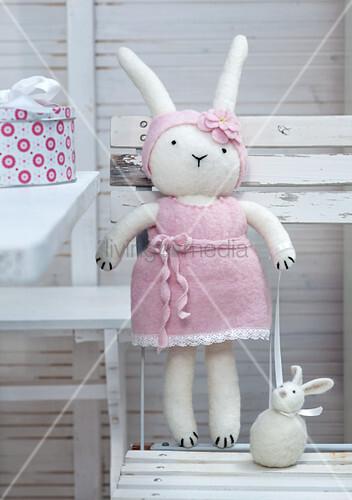 Hand-made, felt Easter bunny on white garden table