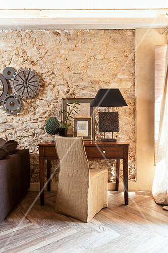 Desk and loose-covered chair in front of stone wall in living room