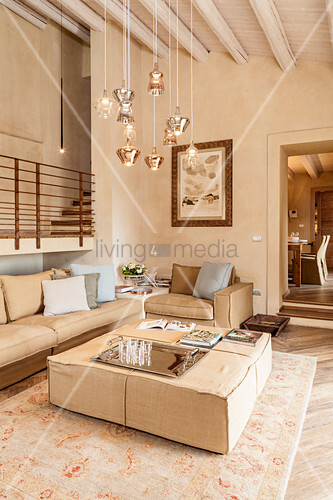 Pale upholstered furniture and designer lamps in stylish living room with raised gallery along one wall