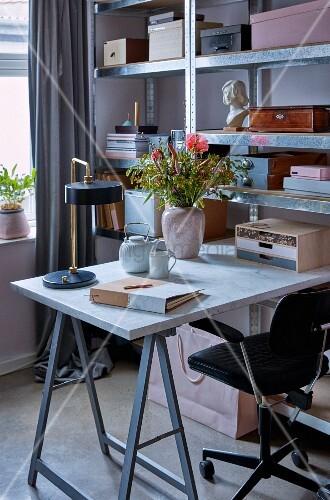 Schreibtisch auf Möbelbock und Metallregal mit Kästen