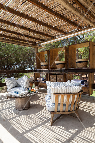 Wooden chairs with cushions on roofed terrace