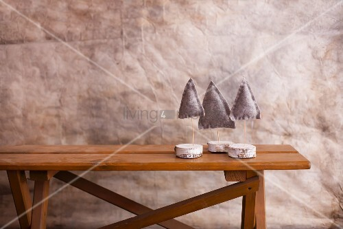 Three small felt Christmas trees on stands made from slices of birch