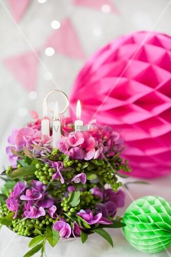 Blumengesteck mit Kerzen auf Etagere und bunte Wabenbällchen