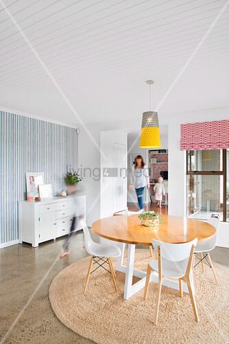 Familie geht durchs moderne Esszimmer mit rundem Tisch