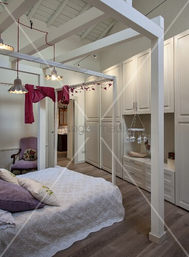 Double four-poster frame above bed in front of fitted wardrobes with panelled doors