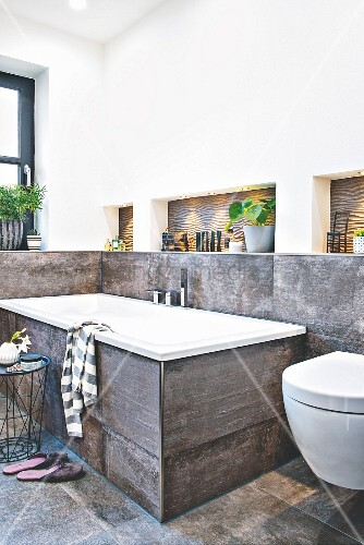 A bath tub with large format, concrete-style tiles