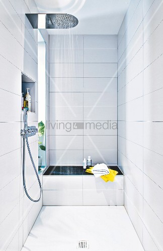 A white tiled shower area with a bench