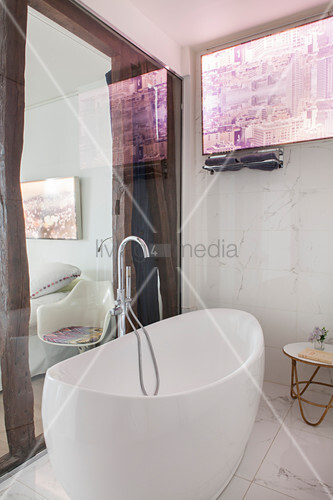 Free-standing bathtub with floor-mounted tap fittings in front of glass wall in ensuite bathroom