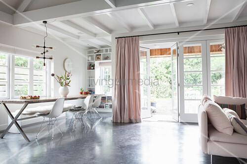 Esstisch mit Klassikerstühlen vor Terrassentür in offenem Wohnraum mit Betonboden