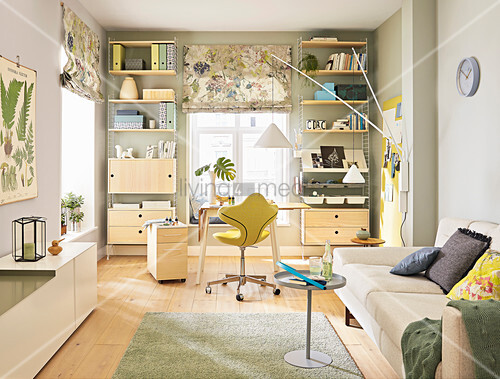 A modular shelving system and a desk by a window in a living room