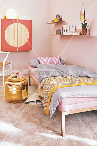 A pink daybed with bedclothes, a golden side table and a wall cupboard