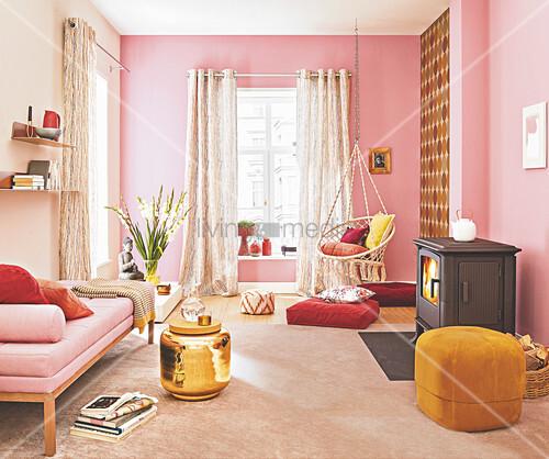 Daybed, Pouf, goldfarbener Beistelltisch, Hängesessell und Holzofen im Wohnzimmer in Rosatönen