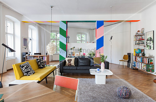 Colourful partition with wide stripes and lounge area in open-plan interior