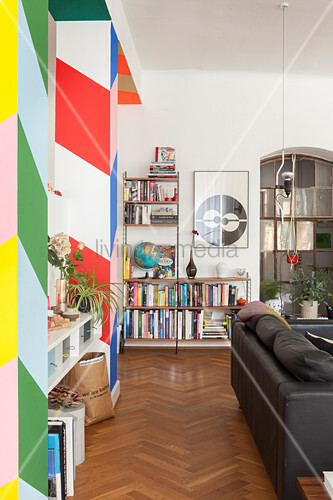 Bunter Raumteiler mit Blockstreifen, davor schwarze Ledercouch und Bücherregal
