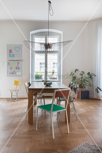 Wooden table and various chairs in front of window in period apartment