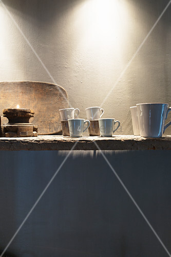 Cups and rustic accessories on shelf made from old board