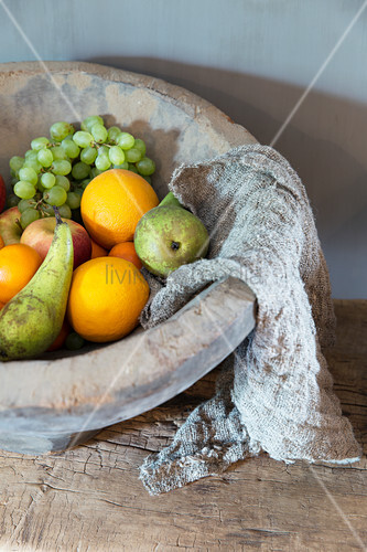 Obst und gewebtes Tuch in einer rustikalen Terracottaschale
