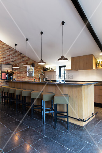 Counter with barstools on black-tiled floor in converted barn