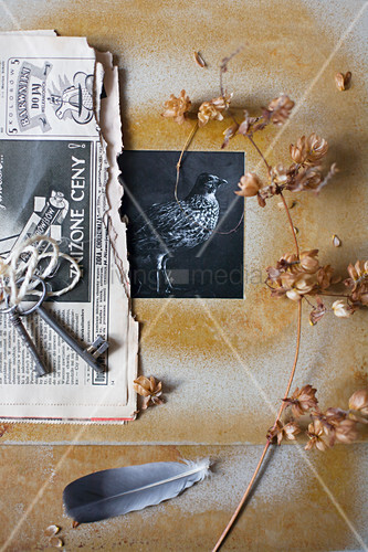 Black-and-white photo in hand-made frame, dried flowers, newspaper and keys