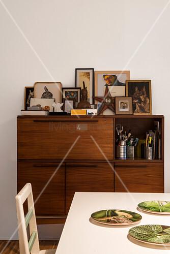 Blick über Esstisch auf Highboard mit Fotos