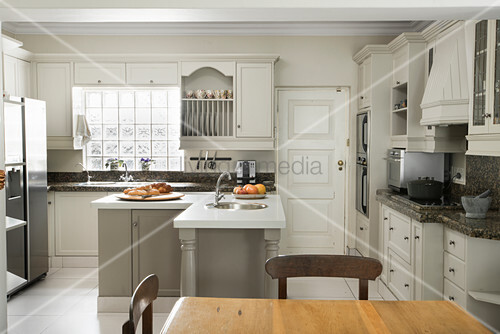 L-shaped counter in renovated country-house-style kitchen with dining area in foreground