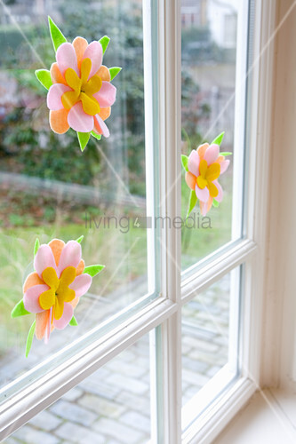 Hand-made felt flowers decorating window for spring
