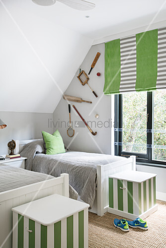 Twin beds and vintage sporting equipment decorating wall in bedroom