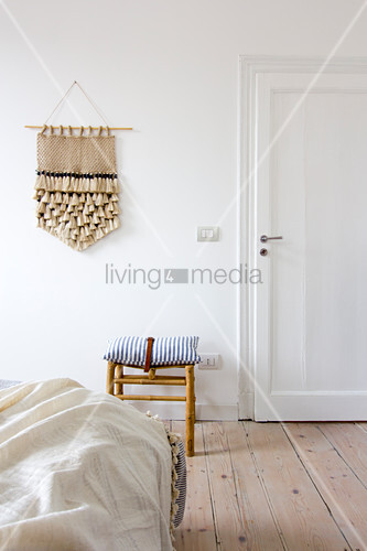 Hand-made wall hanging on white wall in bedroom with wooden floorboards